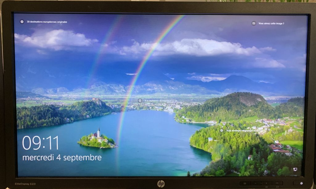 Windows login screen with an aerial view of an island on a lake and a double rainbow